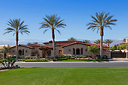 View across grass to façade of luxury suburban villa