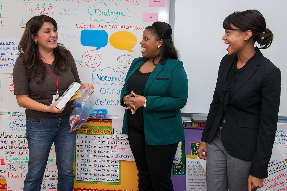 Elsa Simon, left, reacts after receiving an iPad Mini from Houston ISD Human Resource representatives Patra Brannon, center, and Sherelle Foust, right, after winning a drawing from teachers who referred newly hired teachers at Janowski Elementary School, November 25, 2013.
