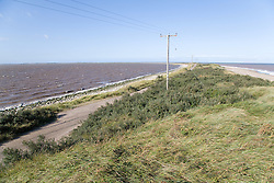 Road and grassy dunes at Spurn Head; East Yorkshire; England; with North Sea on the right and Humber Estuary on the left,