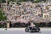 Man riding motorcycle in hill city of Modica Alta looking towards Modica Bassa, Sicily, Italy