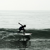 Young surfer slices through the glassy wave off the Pacific Coast Highway, California.