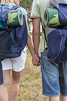 Midsection of young backpackers holding hands in countryside