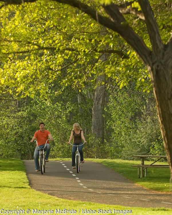 Couple enjoying a cruise while biking on the greenbelt through Ann Morrison Park. Boise, Idaho.    Model Release
