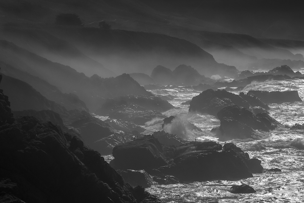 The dramatic Big Sur coastline in California along the Pacific Coast Highway.  Large waves crash into the rocky shoreline along with the early morning mist in the surrounding hills.