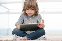 Full length of boy using digital tablet in living room