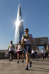 © Licensed to London News Pictures. 24/07/2018. London, UK.  A man reads a book as he walks across London Bridge this morning, whilst the sun reflects off of the London shard during another day of hot and sunny weather in the capital.  Photo credit: Vickie Flores/LNP
