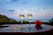 Ad Campaign: Two glasses of Champagne on table overlooking the beach at Grajagan Resort, Ilha do Mel, Brazil