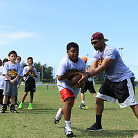AARON STEWART || BUY AT PHOTOS.DJO<br /> 10-year-old Christian Palmer takes the ball from former MSU Football Player Reggie Harris during a running drill at the All-Star Football Camp benefiting the Boys & Girls Club Saturday Morning.