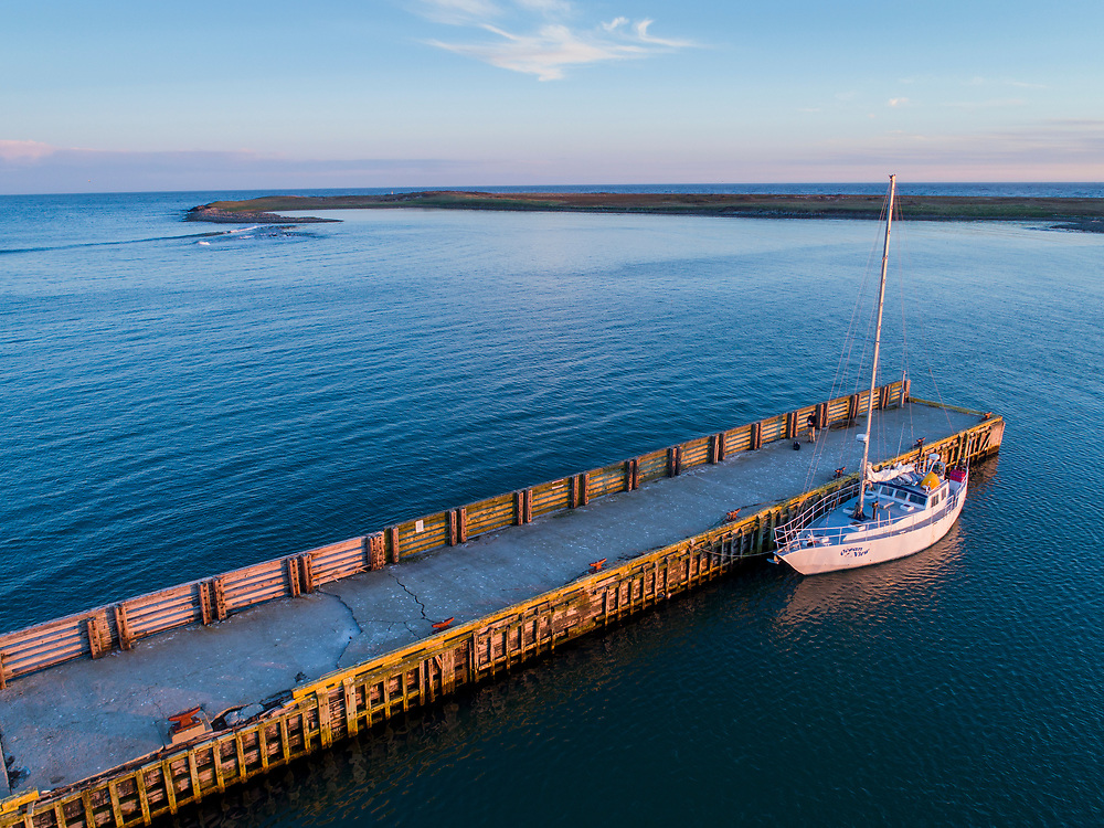 Canada, Newfoundland, Codroy, Aerial view of expedition yacht S/V Ocean View tied up along pier of fishing village on summer evening