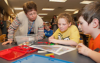 "Paraprofessional Trish Poliquin watches as Alyson VonGeorge and Ayden LaChance work together to build their Lego flipbook during Elm Street School's program ""Let Go Your Mind"" Tuesday afternoon.   (Karen Bobotas/for the Laconia Daily Sun)"