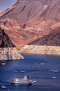 Lake Mead, formed on the Colorado River, above Hoover Dam is a popular tourist, travel and vacation destination. Boaters and passengers of the Desert Princess paddle wheel relax and enjoying themselves in the Black Canyon arm above Hoover Dam