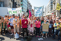 London, UK. 20th April 2019. Supporters of Extinction Rebellion look on as police officers move in to arrest climate change campaigners from Extinction Rebellion who had locked themselves using arm tubes at Oxford Circus following a policing operation to clear it of protesters earlier in the day. The heart of London's shopping district was blocked again for around two hours by the lock-ons on the sixth day of International Rebellion activities to call on the British government to take urgent action to combat climate change.