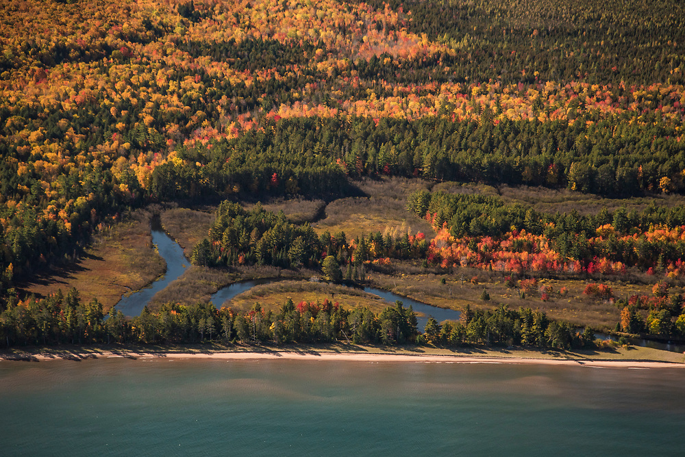 Aerial photography of the mouth of the Salmon Trout River at Lake Superior near Big Bay, Michigan during fall color season.