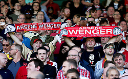 Arsenal fans in the stands hold up scarves to honour outgoing manager Arsene Wenger