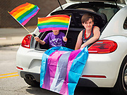 "28 JUNE 2020 - DES MOINES, IOWA: Children with Pride Flags in the back of a car during the Capitol City Pride Parade in Des Moines. Most of the Pride Month events in Des Moines were cancelled this year because of the COVID-19 pandemic, but members of the Des Moines LGBTQI community, and Capitol City Pride, the organization that coordinates Pride Month events, organized a community ""parade"" of people driving through the East Village of Des Moines displaying gay pride banners and flags. About 75 cars participated in the parade.   PHOTO BY JACK KURTZ"