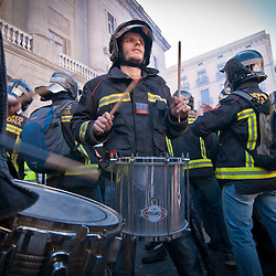 A fire fighter plays a drum during a protest against budget cuts.