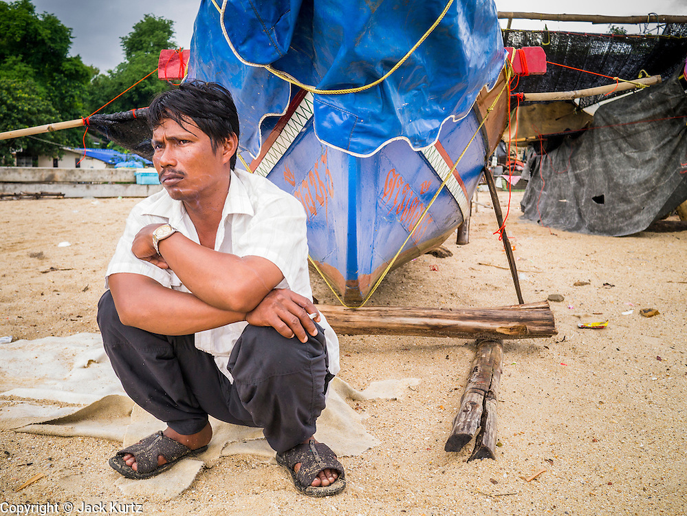 04 NOVEMBER 2012 - KAO SENG, SONGKHLA, THAILAND:  A man sits by the bow of his fishing boat in Kao Seng. Kao Seng is a traditional Muslim fishing village on the Gulf of Siam near the town of Songkhla, in the province of Songkhla. In general, their boats go about 4AM and come back in about 9AM. Sometimes the small boats are kept in port because of heavy seas or bad storms.    PHOTO BY JACK KURTZ