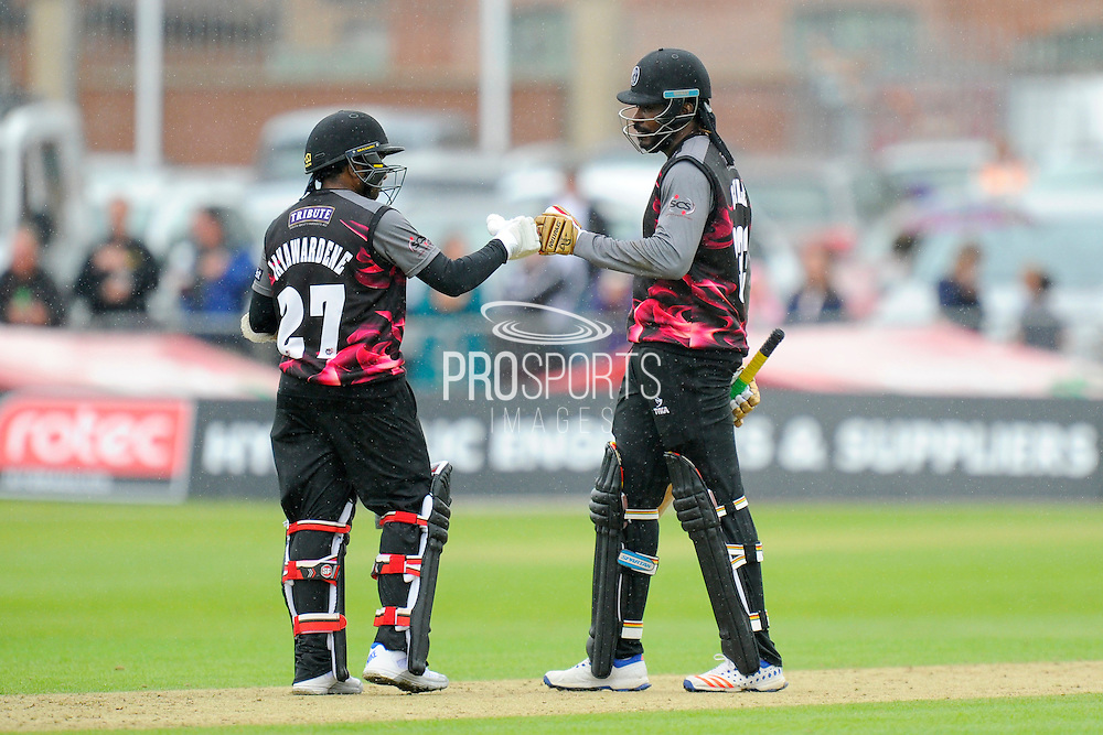 50 for Chris Gale - Somerset's Chris Gayle celebrates scoring his half century with Somerset's Mahela Jayawardene during the NatWest T20 Blast South Group match between Somerset County Cricket Club and Hampshire County Cricket Club at the Cooper Associates County Ground, Taunton, United Kingdom on 19 June 2016. Photo by Graham Hunt.