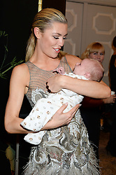 ABBEY CLANCY holding a baby at Fashion For The Brave at The Dorchester, Park Lane, London on 8th November 2013.