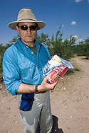 Michael McPherson holds a food pack that No More Deaths volunteers give to migrants they encounter while on patrol in the desert.