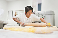 Young male baker working with rolling pin on yellow dough in bakery