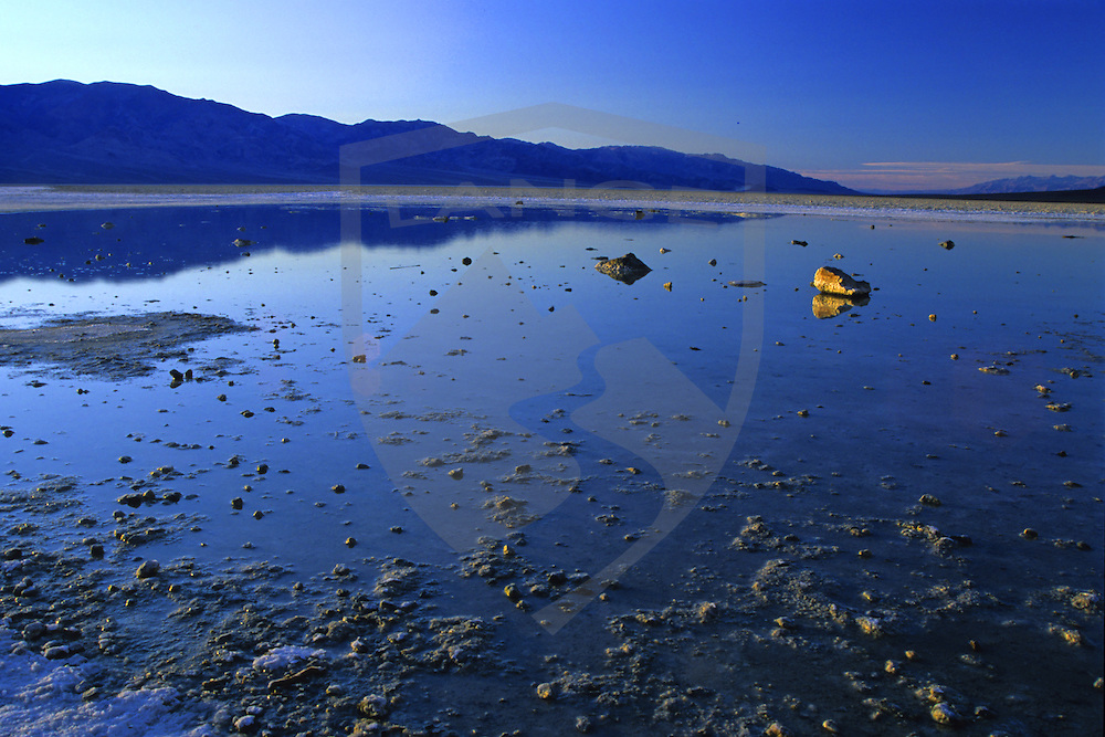 sunset light comes to badwater in death valley national park of southern california.  such beautiful nature scenery and landscapes can be found at death valley, the largest national park in the united states.