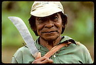 Kanamari Indian man rests machete on shoulder after hike in jungle; Tres Unidos, Amazonas Brazil