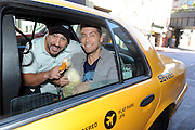 Lance Bass, right, Joey Fatone and the Aflac Duck hop in a taxi on their way to a New York vocal studio session, Monday, Sept. 23, 2013.  The Aflac Duck, in town for Advertising Week, is celebrating his comeback from injuries that left him unable to quack.  (Photo by Diane Bondareff/Invision for Aflac/AP Images)