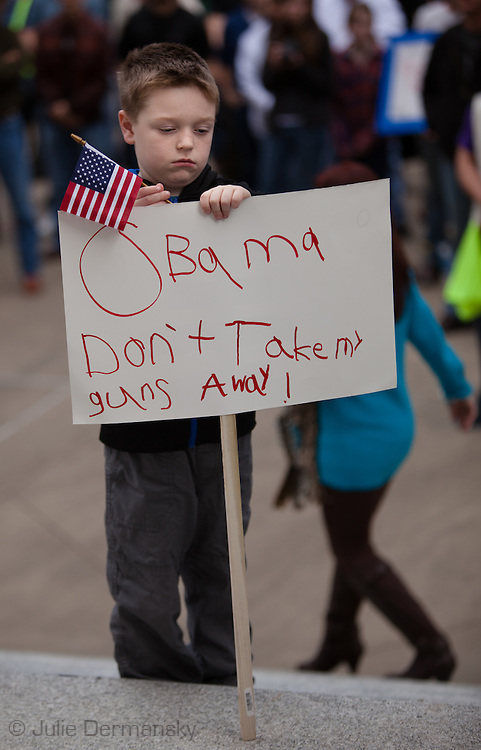 "January 18, Baton Rouge , 7 year old Caden at a pro-gun rally organized by ""Guns across America"" on ""Gun Appreciation Day"", holds a sign with a message for President Obama. His mother read a letter he wrote to the president asking for him to let his teacher and mother have guns during the rally. After the massacre at  a school in Sandy Hook, Connecticut , the debate over gun control in America became a key political issue."