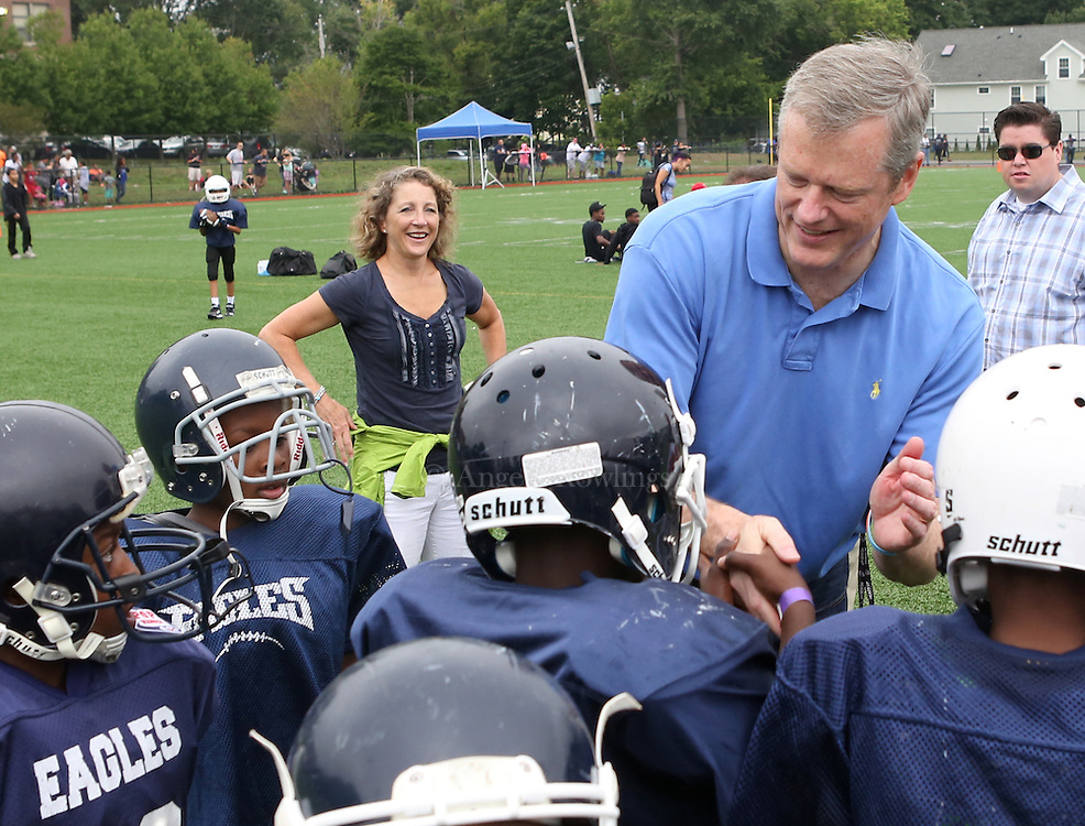 (Boston, MA -- 8/23/15)  Gov. Charlie Baker and his wife, Lauren, greet football players from the Dorchester Eagles during the Boston Mayor's Cup at Roberts Playground in Dorchester, Sunday, August 23, 2015. Staff photo by Angela Rowlings