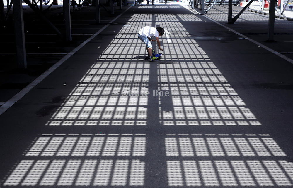 shadow of overhead metal grating projected on playing boy and road