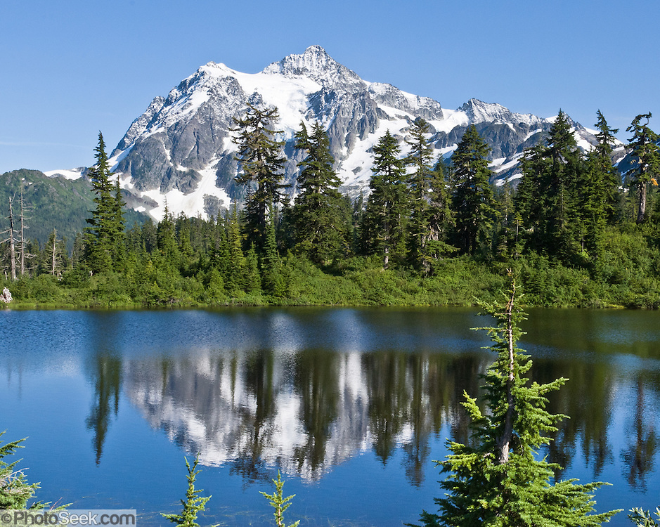 Mount Shuksan reflects in Highwood Lake. Mount Shuksan (9127 feet elevation) is in North Cascades National Park, Washington. Highwood Lake is in Mount Baker-Snoqualmie National Forest.