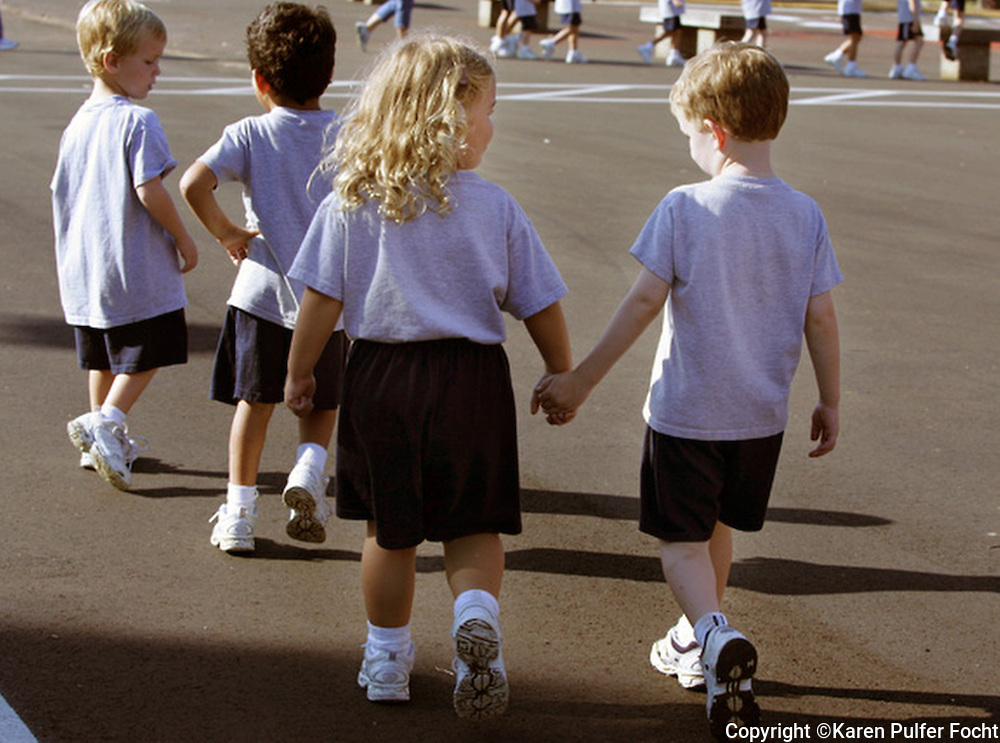 A young boy and girl hold hands on the playground.