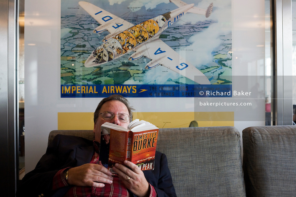 Business traveller reading novel during layover in the British Airways Galleries Club for passengers at Heathrow airport's T5