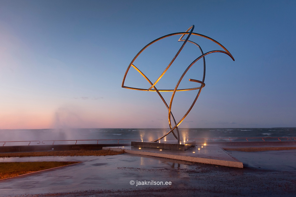 Storm waves crashing over  waterfront promenade and coastline in Tallinn, Estonia. Baltic Sea. Metal sculpture.