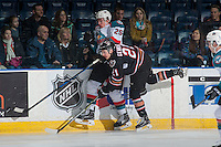 KELOWNA, CANADA - FEBRUARY 1: Matteo Gennaro #21 of the Calgary Hitmen checks Cal Foote #25 of the Kelowna Rockets into the boards on February 1, 2017 at Prospera Place in Kelowna, British Columbia, Canada.  (Photo by Marissa Baecker/Shoot the Breeze)  *** Local Caption ***