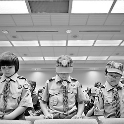 Cub Scout Pack 2 members, (left to right) Alex Wade, Nick Garst, and Ben Coleman, based at Raleigh Court Presbyterian Church, bow their head during the invocation before a City Council Meeting. The Scouts were at City Hall to help learn about civics for their Citizenship badge.