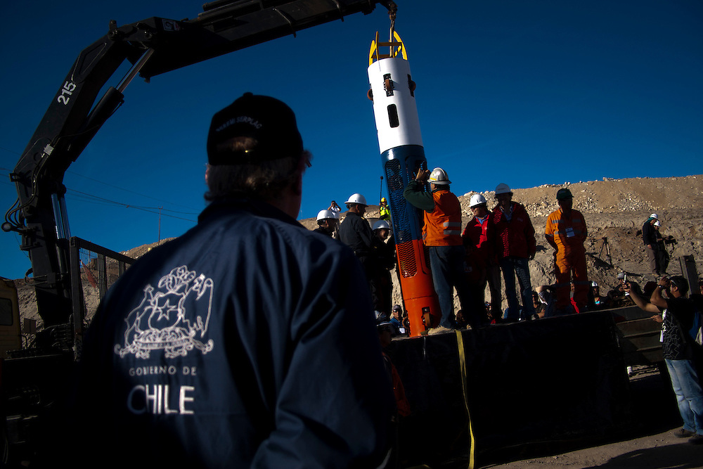 """Members of the rescue team shows the capsule where will be rescue the 33 miners trapped at San Jose Mine. From August 5th, 33 miners are trapped after a cave-in at San Jose Mine in the north of Chile. 17 days after these miners were discovered, alive. More of two months after they will be rescue. All this time some families stay out side the mine borders waiting for news and theses parents, the past of the days gives place a little town knows as """"Camp Hope""""."""