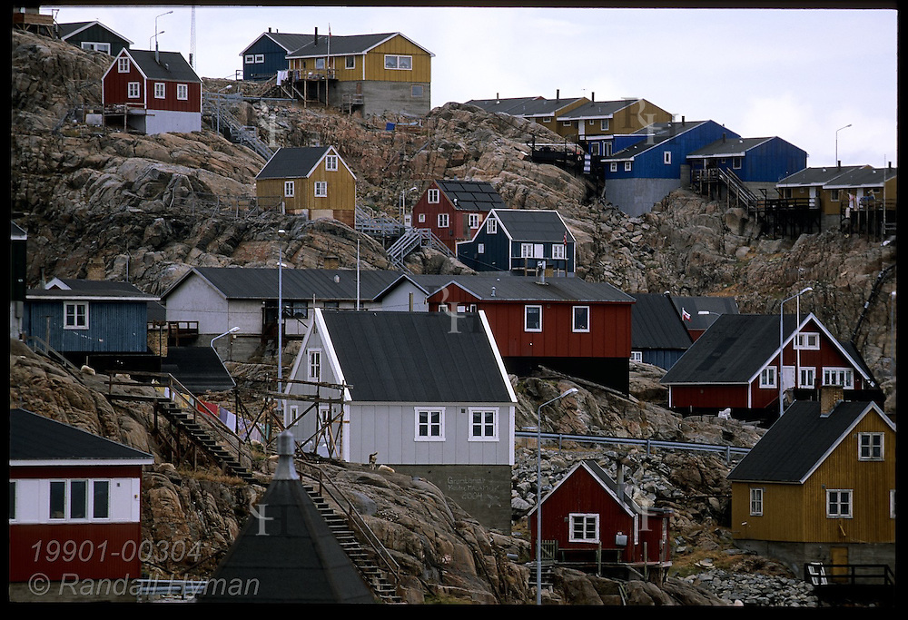 Colorful, Danish-style wooden homes cling to rocky slopes at the island town of Uummannaq, a former whaling station; Greenland