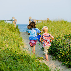 A young brother and sister walk at Center Hill Preserve beach in Plymouth, Massachusetts.  Model Released.