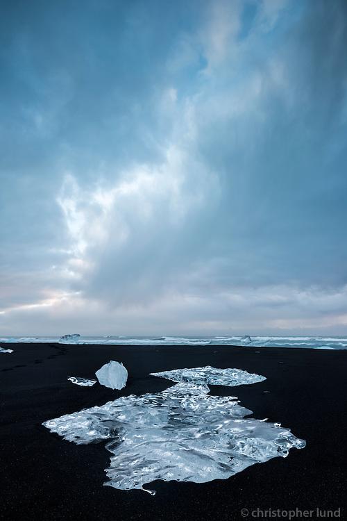 Blue icebergs on the black sand beach below Jökulsárlón glacial lagoon.