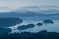 Fulford Harbour and the receding mountain ranges of the Gulf Islands and Vancouver Island are seen from the top of Mount Maxwell on Salt Spring Island.  Gulf Islands, British Columbia, Canada.
