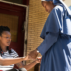 Teak Phillips | St. Louis Review | @TeakPhillips<br /> <br /> Sister Mary Paschal of the Society of the Mother of Peace went door-to-door prayed with Carlotta Williams, who lives in the 5300 block of Maple Avenue in the Visitation Park neighborhood.