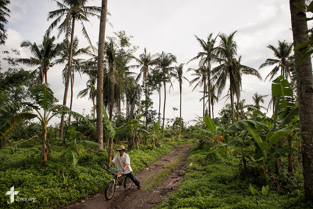 A man rides his bicycle through a muddy road near Mahayag, Leyte Province, Philippines, on Saturday, March 15, 2014. LCMS Communications/Erik M. Lunsford