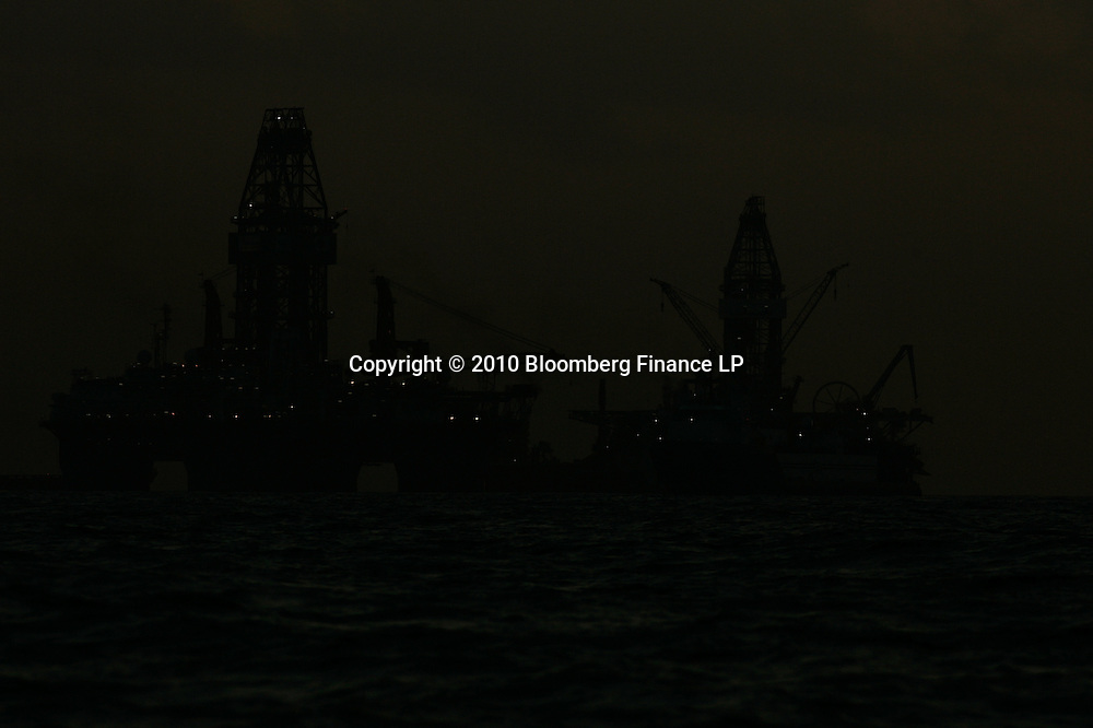 The Transocean Development Driller III and Transocean Development Driller II are seen lit up in the night sky at the BP Plc Macondo well site in the Gulf of Mexico off the coast of Louisiana, U.S., on Thursday, July 29, 2010. BP Plc continues to work on a relief well to permanently plug the source of the largest oil spill in U.S. history.  Photographer: Derick E. Hingle/Bloomberg