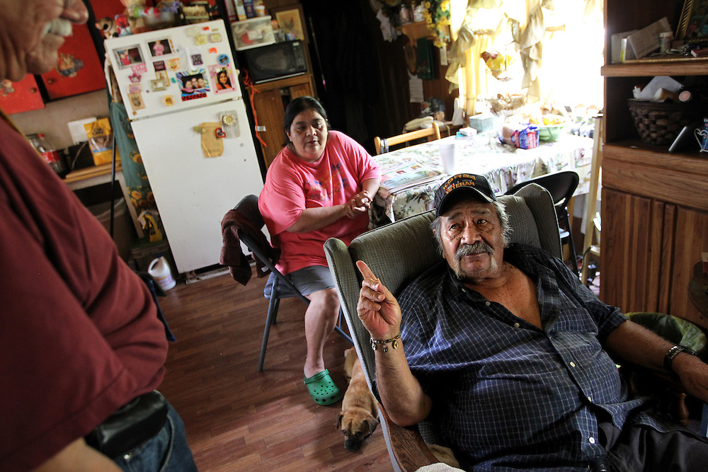 Esteban Aguilar, right, tells community activist Lionel Lopez, left, about how his house shakes when trains pass on the nearby railroad in Banquete, a colonia outside of Corpus Christi, June 2, 2010. Aguilar's daughter, Mary Jane Aguilar, center, lives with her father and helps take care of him. Lopez periodically checks in with them, inquiring about water quality and any pressing needs they may have. (Courtney Perry/The Dallas Morning News). 09122010xNEWS