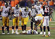 Pittsburgh Steelers wide receiver Antonio Brown (84) lies on the ground after a hard hit at the end of the game by Cincinnati Bengals outside linebacker Vontaze Burfict (55) as he gets attention from Pittsburgh Steelers wide receiver Markus Wheaton (11), Pittsburgh Steelers guard David DeCastro (66), Pittsburgh Steelers center Cody Wallace (72), Pittsburgh Steelers offensive tackle Byron Stingily (79), and Cincinnati Bengals strong safety George Iloka (43) during the NFL AFC Wild Card playoff football game against the Cincinnati Bengals on Saturday, Jan. 9, 2016 in Cincinnati. The Steelers won the game 18-16. (©Paul Anthony Spinelli)