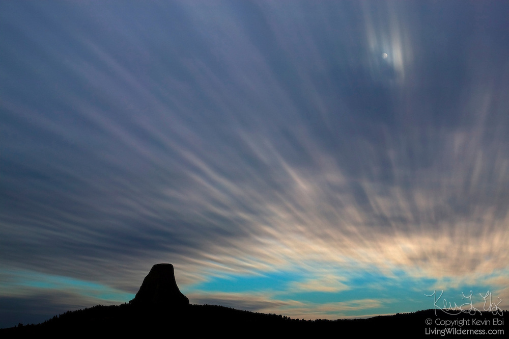 Clouds, lit by the full moon, streak by Devils Tower National Monument in Wyoming. Thinner parts of the clouds caught the moons light; the streaks are the result of a four-minute exposure.