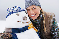 Woman embracing snowman portrait close up