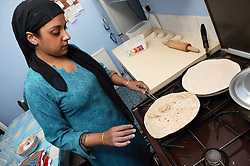 Woman making chapatti's in her kitchen,